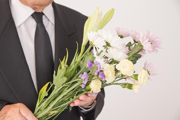 菊や百合を手にしているスーツ姿の男性